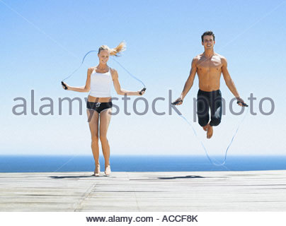 A man and a woman working out with jump ropes - Stock Photo