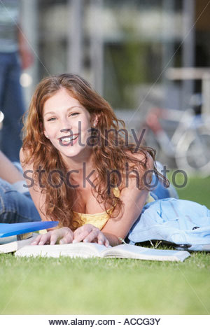 Young Woman laying down on grass with books - Stock Photo