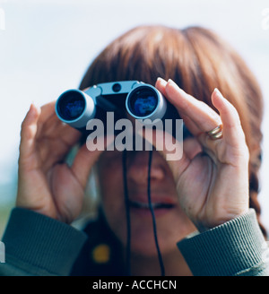 A woman looking in a pair of binoculars. - Stock Photo