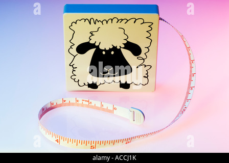 Open measuring tape coiled round on a colourful background - Stock Photo