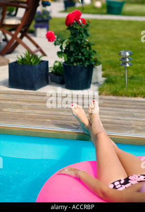 Feet resting by a pool edge. - Stock Photo