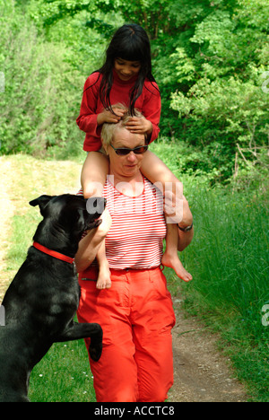 MR PR black dog and young dark haired girl in age of 6 years in nature sitting on shoulders of a middle aged woman - Stock Photo