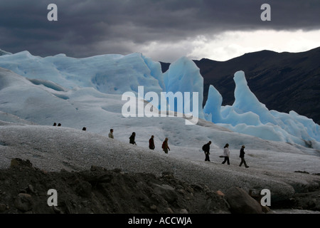 View of the Perito Moreno glacier in Patagonia, Argentina, South America. Line of tourists trekking on ice field - Stock Photo