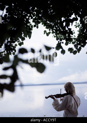 A man playing the violin by a lake. - Stock Photo