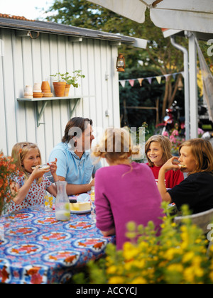 Family having dinner in their garden. - Stock Photo