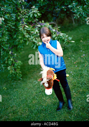 A girl riding on a hobbyhorse. - Stock Photo