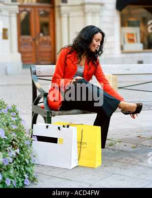 A woman resting her feet after shopping. - Stock Photo
