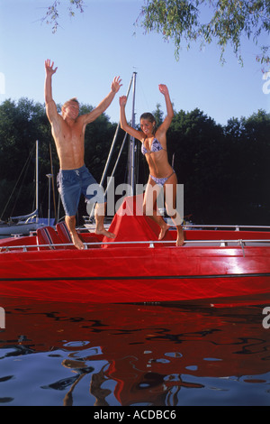 Young couple jumping off red boat into cold water - Stock Photo