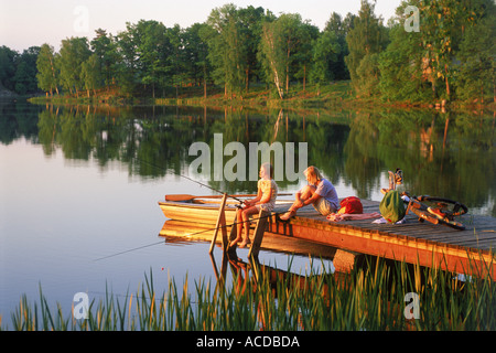 Two girls fishing off lake pier at dusk in Sweden - Stock Photo
