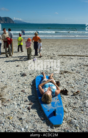 Woman rests on a surf board on Keel beach, Achill Island, Ireland - Stock Photo