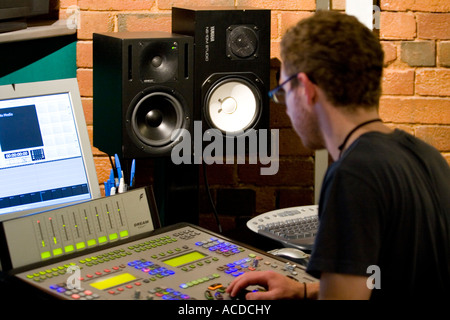young man mixing at sound desk console mixer in recording studio - Stock Photo