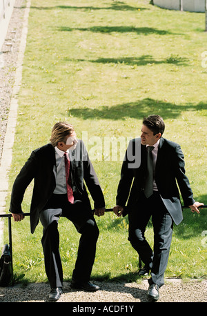 Two businessmen sitting on a railing next to a lawn. - Stock Photo