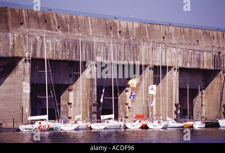 Racing yachts moored in front of the giant German built submarine base in Saint Nazaire Brittany France - Stock Photo