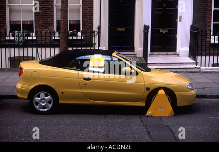 Yellow sports car clamped on residential street, Camden, London. Sign on car window reads: 'Removal of Untaxed Vehicle'. - Stock Photo