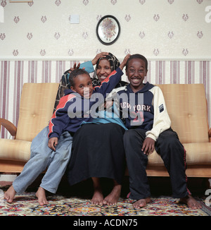 A single mother from Somalia with two of her children in their living room, UK. - Stock Photo