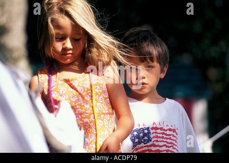 A brother and sister playing outside. - Stock Photo