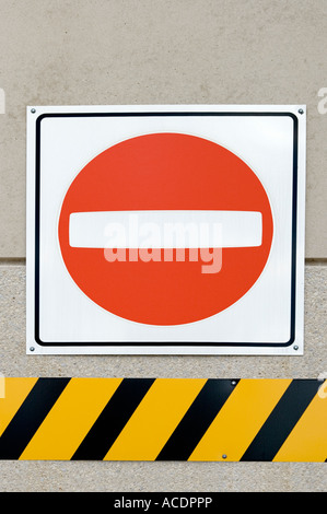 No entry sign over black and yellow striped warning sign - Stock Photo