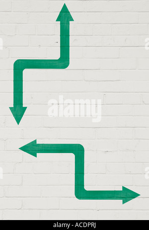 Two bi-directional arrows painted on white brick wall - Stock Photo
