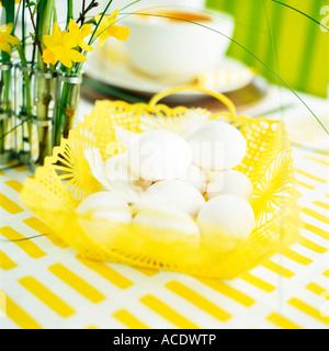 Eggs in a basket on an easter decorated table close-up. - Stock Photo