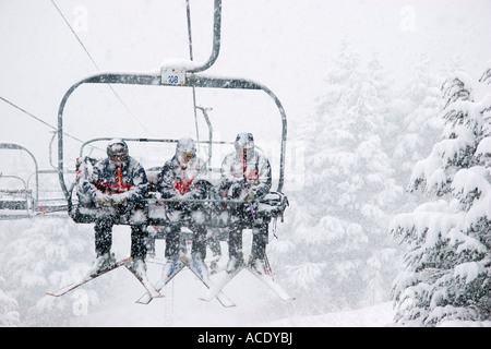 Three male skiers ride a chairlift in the snow at Alyeska Ski Resort in Girdwood Alaska - Stock Photo