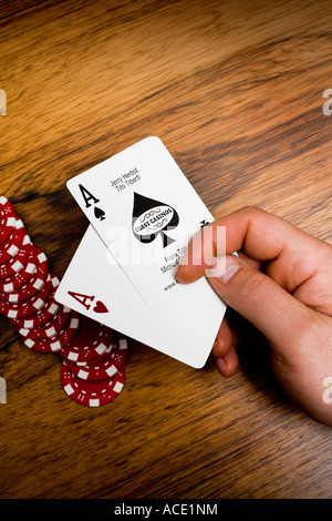 A hand holding two aces gambling marks in the background. Close-up. - Stock Photo