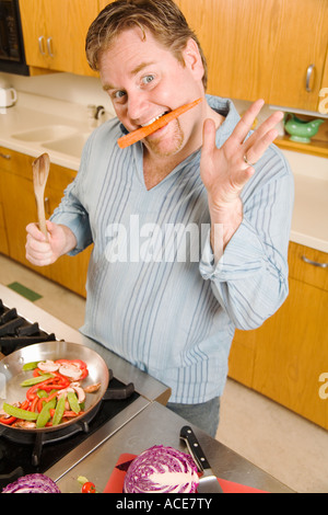 Man playing with food while cooking - Stock Photo