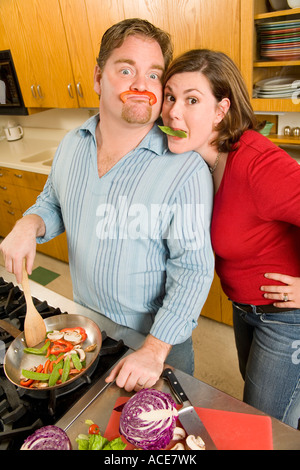 Couple playing with food while cooking - Stock Photo