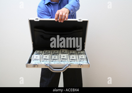 Man holding open briefcase full of money - Stock Photo