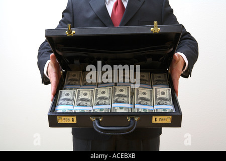 Businessman holding open briefcase full of money - Stock Photo
