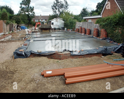 Labourer & work in progress on recently delivered wet ready mix concrete pour to substructure floor slab  to new - Stock Photo