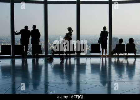 Silhouette of diverse people looking out a picture window atop an observation tower in Tokyo - Stock Photo