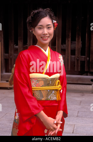 Young woman posing for photo wearing her finest red silk kimono - Stock Photo
