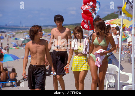 Two couples wearing swimsuits walk along the beach at the Sea of Japan - Stock Photo