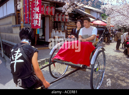 Tourists take a ride in a rickshaw along the Philosophers Path on a spring afternoon - Stock Photo