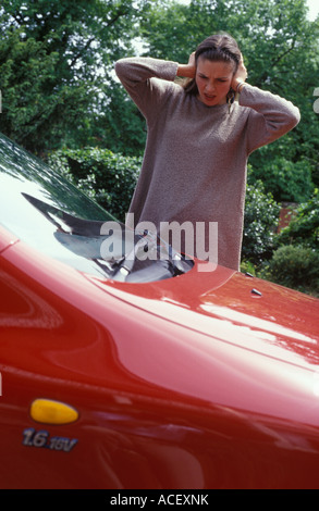 Woman trying to turn her car alarm off - Stock Photo
