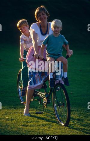 Woman 2 boys on bike - Stock Photo