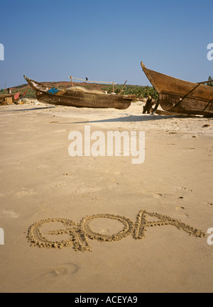 India word Goa written in sand by fishing boats - Stock Photo