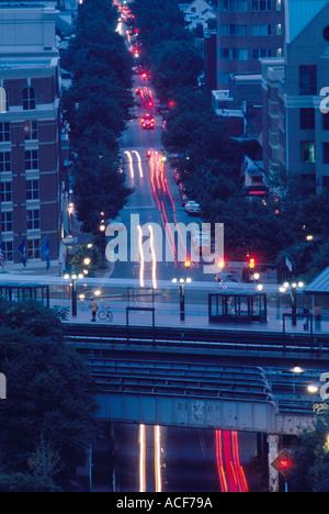 Evening traffic on King St passes beneath the King Street Metro Station in Alexandria VA - Stock Photo