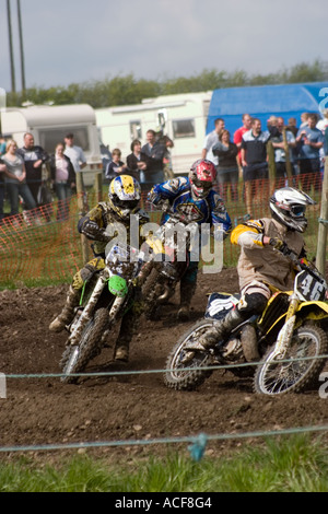 Group of Motocross riders cornering during race - Stock Photo