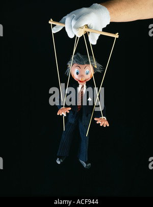 Businessman in a suit puppet being operated by a puppeteer - Stock Photo