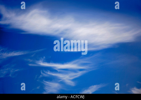 White Cirrus clouds in a bright blue polarised sky - Stock Photo