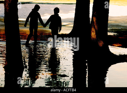 Two children walking in water - Stock Photo