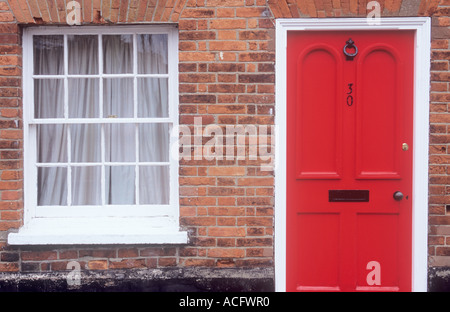 Part of a stylish Georgian terrace house showing fine brickwork sash window and bright red front door - Stock Photo