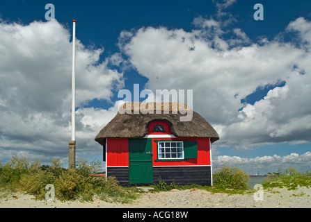 Old small red beach house with tatched roof Marstal Denmark - Stock Photo