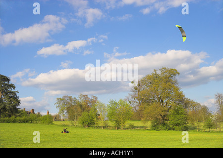 Man flying kite from landboarding buggie above Loseley Park House - Stock Photo