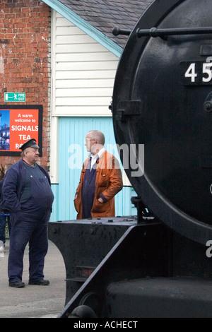 Railway men chat beside steam train 45212 at Grosmont N Yorks UK - Stock Photo