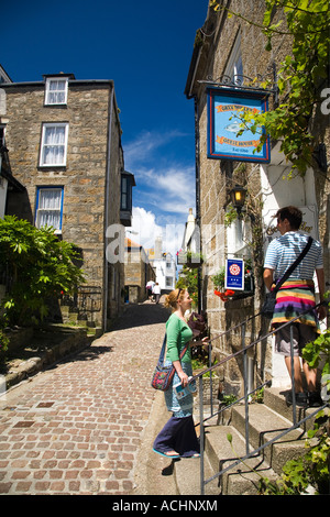 Young couple check into Bed and Breakfast accommodation in narrow street in summer sun sunshine St Ives Cornwall - Stock Photo