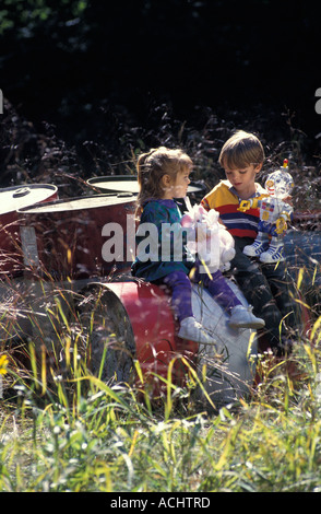 Two Caucasian children playing on barrels of industrial waste in a meadow - Stock Photo