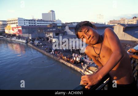 Philippines Boy on Quezon Bridge above Pasig River in Manila - Stock Photo
