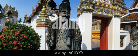 Asia Thailand Bangkok Statue along walls of Thanon Chetuphon on grounds of Wat Pho the oldest largest Buddhist temple - Stock Photo